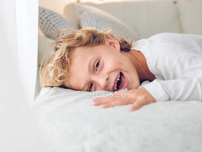 Cute cheerful boy lying on sofa and looking at camera — Stock Photo