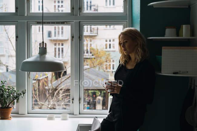 Романтичная блондинка женщина, стоя с Кубка в окно дома — стоковое фото
