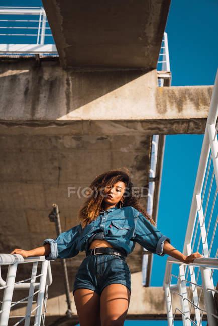 Giovane donna in denim vestiti in piedi su una scala e tenendo ringhiere — Foto stock