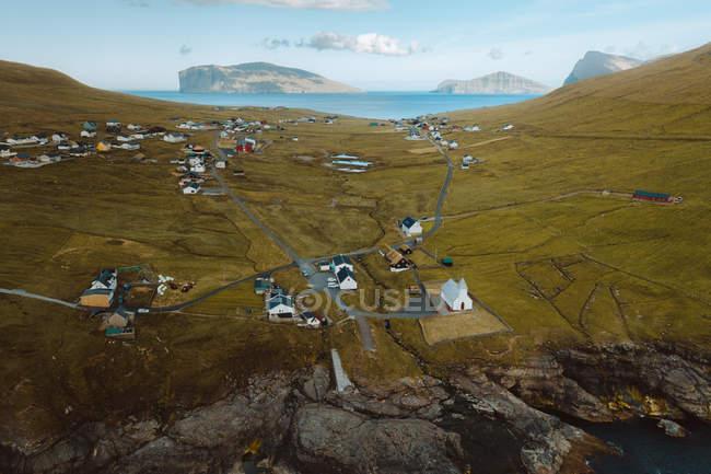 Vue aérienne du petit village dans les collines verdoyantes sur les îles Feroe — Photo de stock