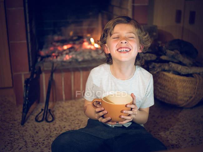 Fröhlicher kleiner Junge sitzt mit Tasse am heimischen Kamin — Stockfoto