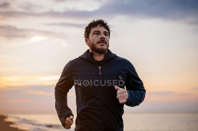 Homem barbudo no sportswear correndo na areia no mar, durante o exercício ao ar livre na praia ao pôr do sol — Fotografia de Stock