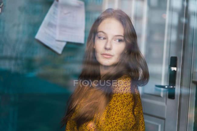 Porträt einer verträumten hübschen Frau, die zu Hause steht und wegschaut — Stockfoto