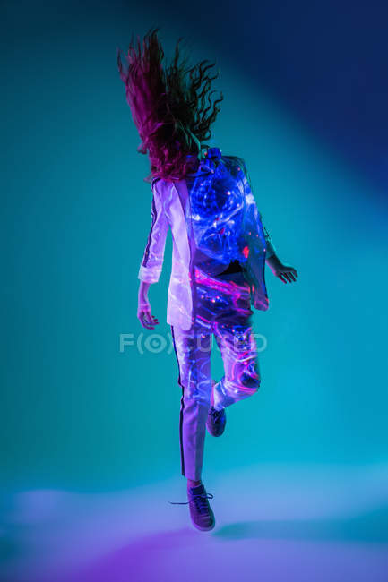 Unrecognizable young woman shaking hair and jumping in ultraviolet and neon light — Stock Photo