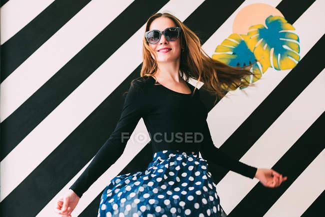 Веселий молода жінка танці барвисті стіни — стокове фото