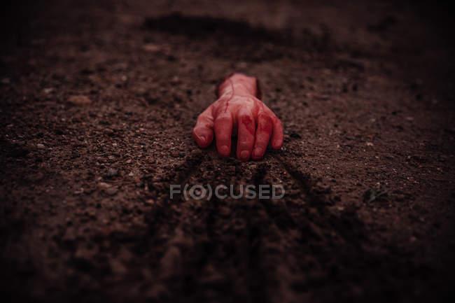 Mano di taglio sanguinosa trascinando a terra — Foto stock