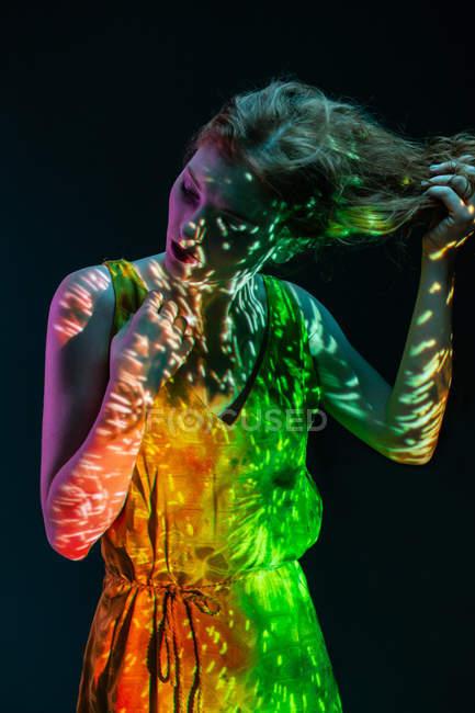 Donna da sogno in calda luce colorata e capelli toccanti — Foto stock