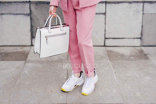 Close-up of stylish model in sneakers and pink suit — Stock Photo