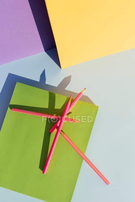 Lápis cor-de-rosa sobre livro verde, no espaço de formas geométricas e sombras fortes. Voltar ao conceito de escola — Fotografia de Stock