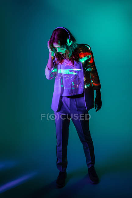 Woman enjoying music with headphones and posing in neon light — Stock Photo