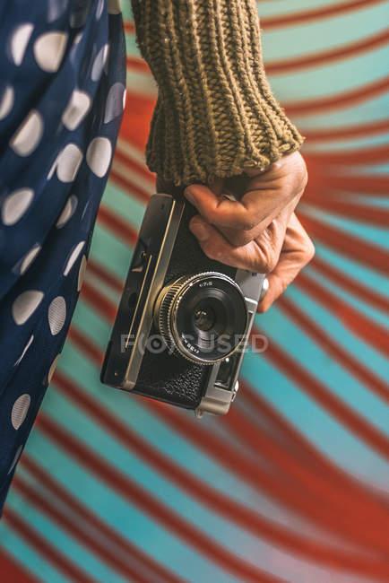 Mão de mulher segurando câmera vintage contra parede colorida modelada — Fotografia de Stock