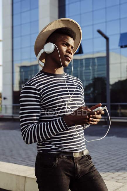 Black man in headphones using smartphone — Stock Photo