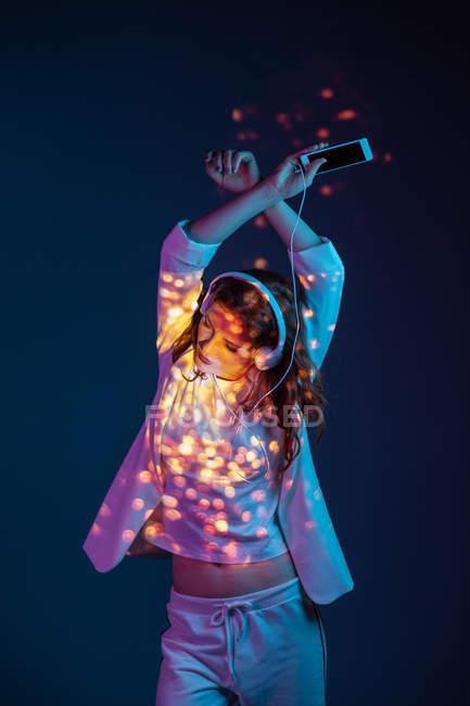 Жінка, насолоджуючись музики з смартфон і навушники в плям яскраве світло — стокове фото