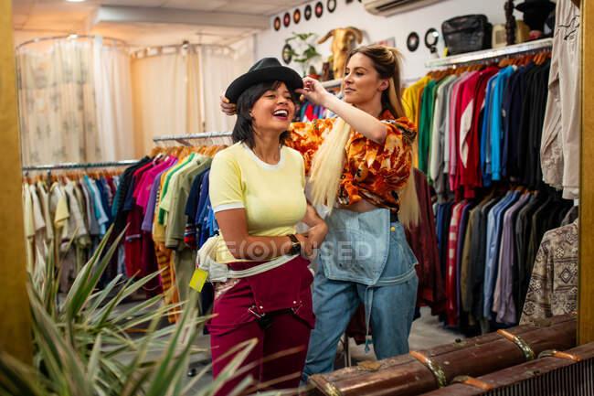 Duas jovens mulheres sorrindo e experimentando um chapéu elegante enquanto estão perto do espelho em uma pequena loja — Fotografia de Stock