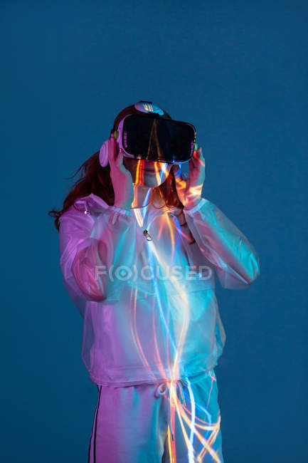 Woman using VR glasses on background with neon light — Stock Photo