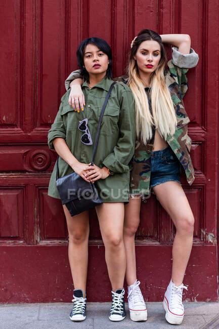 Дві молоді панночки в модних костюмах, що стоять на стіні будинку в сонячний день. — стокове фото