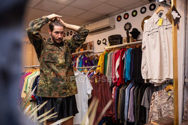 Hombre alegre eligiendo ropa y accesorios en la tienda - foto de stock