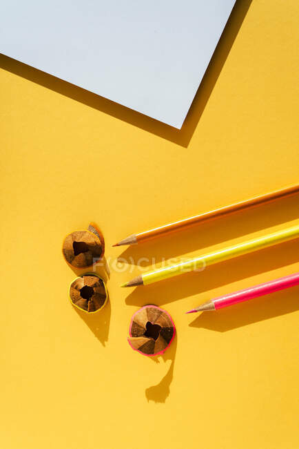 Back to school, Color pencil and shavings from sharpening on yellow background — Stock Photo