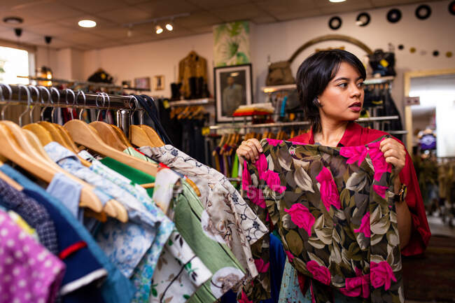 Bastante joven hembra sonriendo y recogiendo prendas de vestir de carril de ropa mientras pasa tiempo en una pequeña tienda - foto de stock