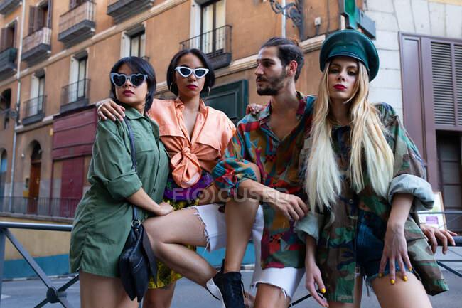 Gruppe junger Leute in trendigen Outfits sitzt auf einem Zaun an der Stadtstraße und schaut weg — Stockfoto