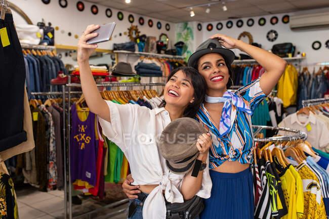Веселые друзья примеряют шляпу в магазине и делают селфи — стоковое фото