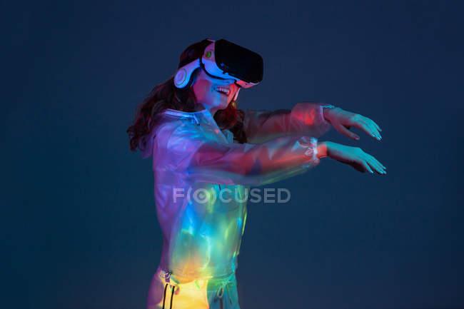 Женщина касается воздуха в VR очки в неоновом свете на темно-синем фоне — стоковое фото