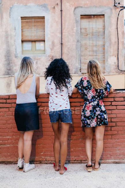 Three girls posing with their backs on the street — Stock Photo