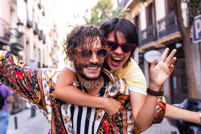 Красивый бородатый мужчина в модном наряде улыбается и катает на спине веселую девушку на размытом фоне городской улицы — стоковое фото