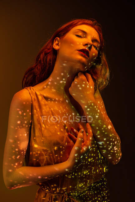 Sensual elegant woman posing in warm light in dark room — Stock Photo