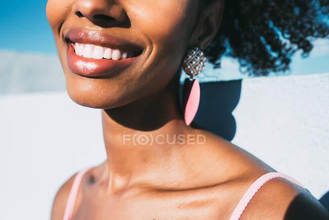 Mulher negra bonita sorrindo usando brincos grandes — Fotografia de Stock