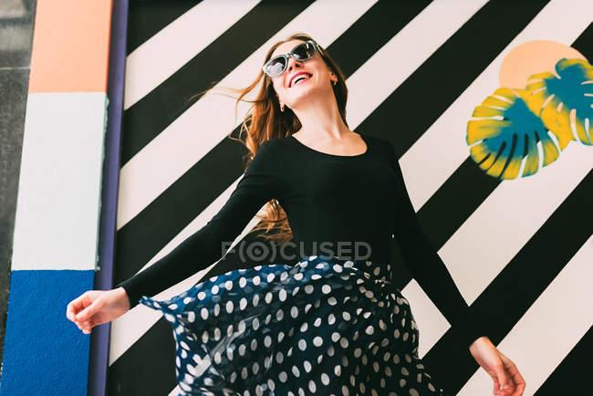 Веселая молодая женщина танцует у цветной стены — стоковое фото