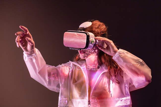 Junge Frau berührt Luft und trägt Virtual-Reality-Headset in rosa Neonlicht — Stockfoto
