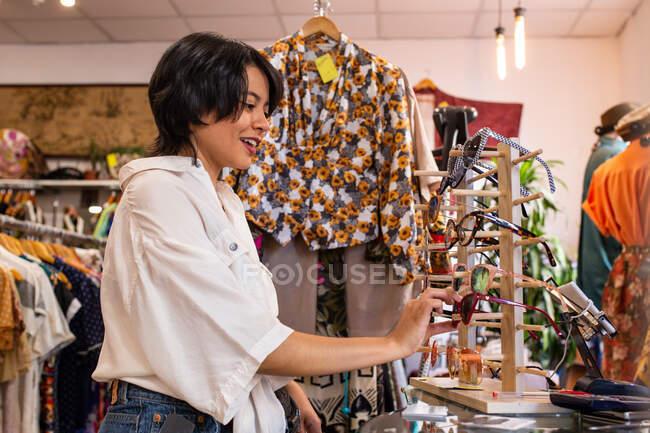 Красивая молодая женщина улыбается и собирает солнечные очки в маленьком магазине — стоковое фото