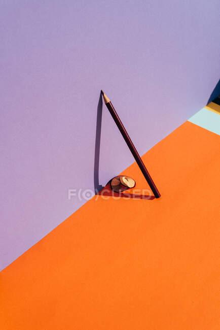Crayon et copeaux d'affûtage, appuyés contre la paroi violette, réfléchissant l'ombre avec une lumière directe. Concept de retour à l'école — Photo de stock