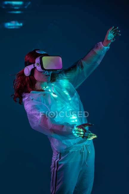 Woman touching air in VR glasses in neon light — Stock Photo