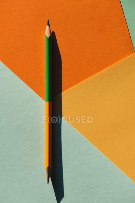 Crayon de couleur double extrémité, sur fond géométrique bleu clair et orange, concept de retour à l'école — Photo de stock