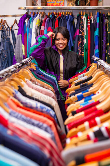 Pretty young woman leaning on clothes rails and looking at camera while standing in small store — Stock Photo