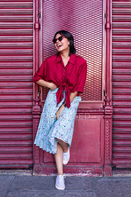 Beautiful young female in trendy outfit laughing and looking away while leaning on burgundy wall on city street — Stock Photo