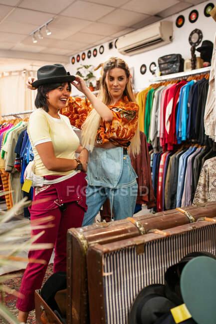 Dos mujeres jóvenes sonriendo y probándose un sombrero elegante mientras están de pie cerca del espejo en una pequeña tienda - foto de stock