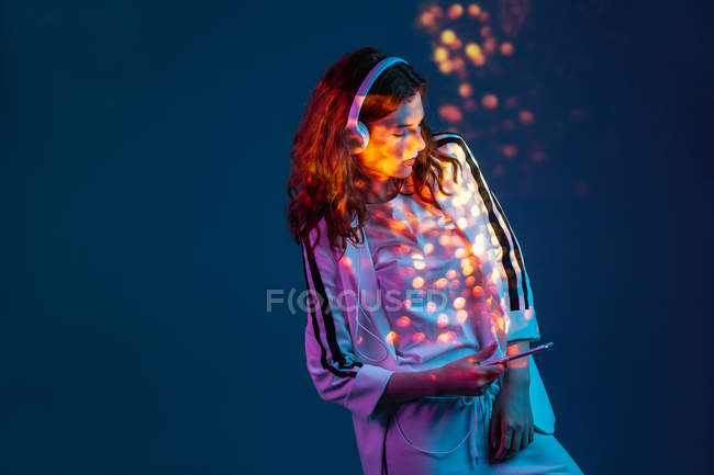 Woman enjoying music with smartphone and headphones in neon light — Stock Photo