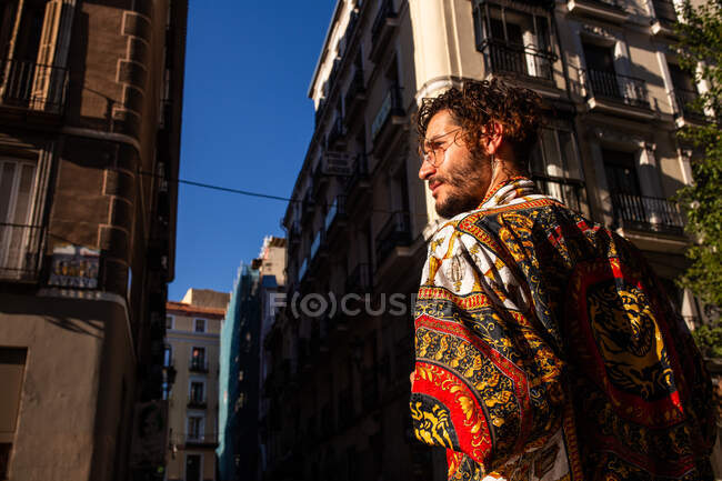 Back view of young guy in stylish outfit walking on street of beautiful city and looking away — Stock Photo