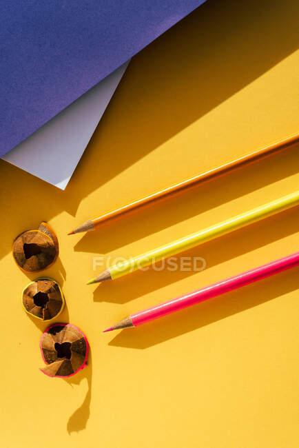 Ritorno a scuola, matita di colore e trucioli da affilatura su sfondo giallo e blu — Foto stock