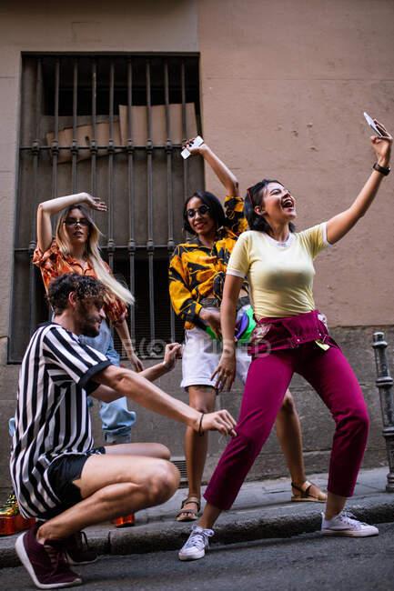 Группа молодых людей в модных нарядах смеется и делает селфи, веселясь на городской улице — стоковое фото
