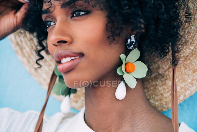 Mulher negra bonita usando brincos grandes e um chapéu de palha — Fotografia de Stock