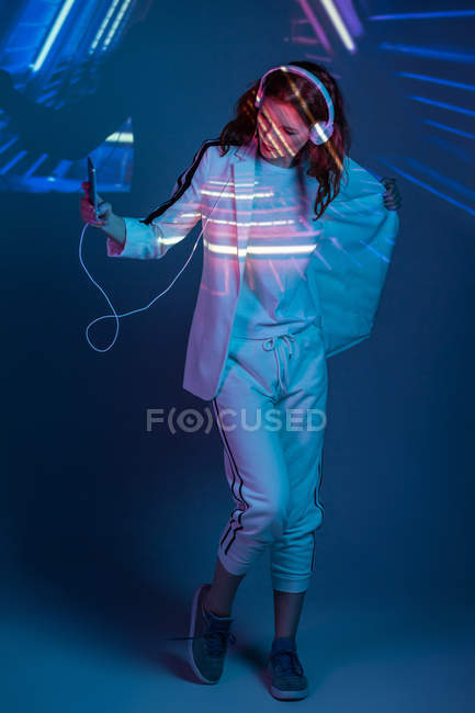 Woman in headphones looking at projection of neon light — Stock Photo