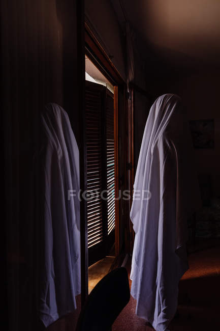Person disguised as ghost for Halloween standing in dark room — Stock Photo
