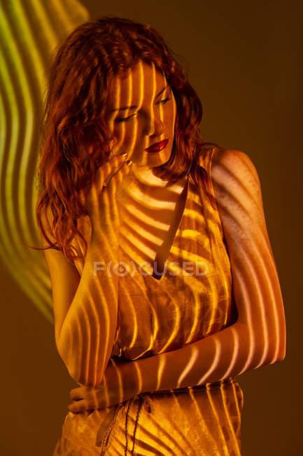Портрет мрійливий жінка в смужку тепле світло — стокове фото