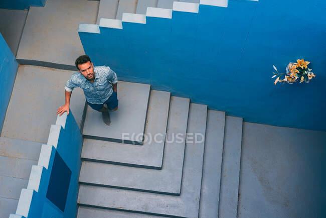 Хитрий чоловік, що стоїть у синіх сходах. — стокове фото