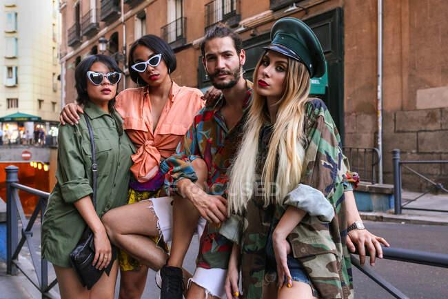 Grupo de jóvenes en trajes de moda sentados en la valla en la calle de la ciudad y mirando hacia otro lado — Stock Photo