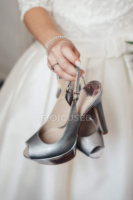 Crop unrecognizable bride holding and showing gray silver shoes. — Stock Photo